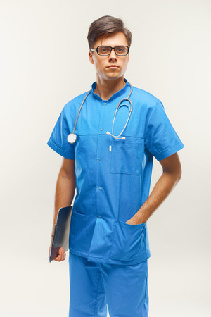 medical occupation: Doctor With Stethoscope Around his Neck Against Grey Background