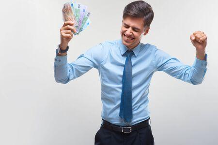 business money: Businessman celebrating money income against white background