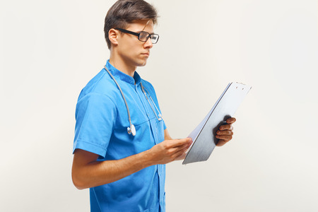 medical occupation: Doctor With Clipboard Against Grey Background Stock Photo