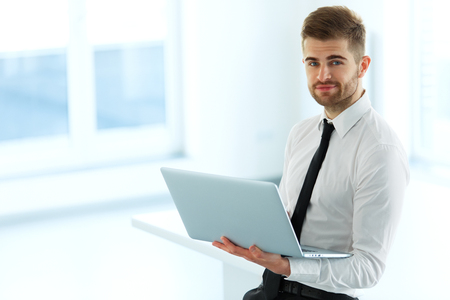 man with laptop: Handsome Businessman Working on Laptop at His Office