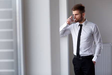 Businessman Thinking about Future of Company. Glass of Water Imagens