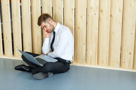 laptop computer: Depressed Businessman sitting on floor at his office. Hard work and stress concept