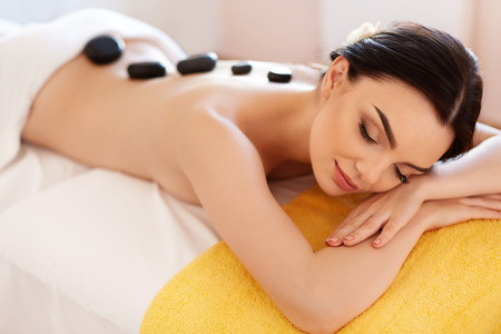 stones: Spa Stone Massage. Young Woman Have Hot Stone Massage Treatments. Spa Hot Stones
