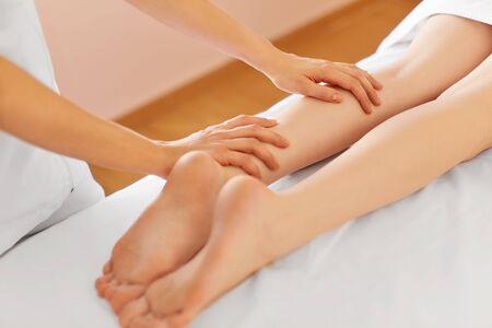 reflexology: Young Woman Receiving Leg Massage at Spa Center. Body Care