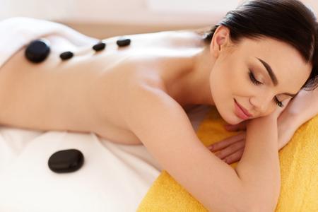 cuerpo femenino: Spa Masaje con piedras. Mujer joven que los tratamientos de masaje de piedra caliente. Spa de piedras calientes