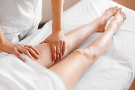 body care: Young Woman Receiving Leg Massage at Spa Center. Body Care