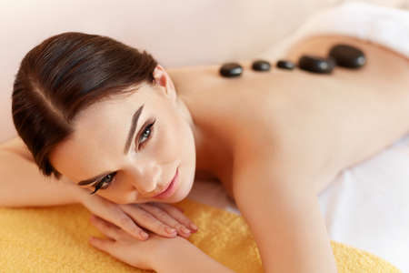 spa woman: Spa Stone Massage. Young Woman Have Hot Stone Massage Treatments. Spa Hot Stones
