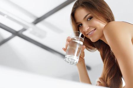 agua potable: Salud, belleza, concepto de dieta. Retrato de feliz sonriente mujer joven refrescante agua potable en la mañana. Cuidado de la salud. Bebidas. Alimentación saludable. Estilo de vida saludable. Hidratación.