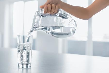 fitness: Beber agua. Mão da mulher derramando água pura fresca do jarro em um copo. Saúde e dieta Concept. Estilo de vida saudável. Cuidados de Saúde e Beleza. Hidratação.
