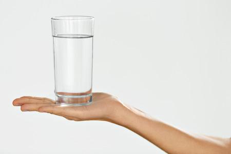 acqua bicchiere: Bicchiere d'acqua. Salute e la dieta concetto. La detenzione di vetro mano della donna. Alimentazione sana,. Bevande. Sanità e bellezza. Idratazione