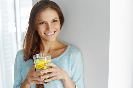 Healthy Lifestyle, Food. Happy Woman Drinking Summer Refreshing Fruit Flavored Infused Water With Fresh Organic Lemon, Lime, Mint. Detox Vitamin-fortified Water. Healthy Eating. Vitamin, Diet Concept.