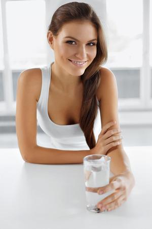 agua potable: Salud, belleza, dieta concepto. Retrato de mujer feliz sonriendo joven que bebe refrescante agua en la mañana. Cuidado de la salud. Bebidas. Alimentación saludable. Estilo de vida saludable.
