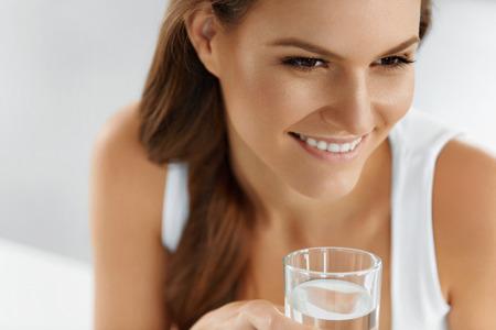 vasos de agua: Salud, belleza, dieta concepto. Primer plano Retrato de mujer feliz joven que bebe agua pura Refrescante De Cristal. Cuidado de la salud. Bebidas. Agua. Alimentación saludable. Estilo de vida saludable.