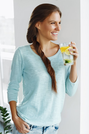 vasos de agua: Healthy Lifestyle. Happy Woman Drinking Lemonade With Fresh Lemon, Lime And Mint In Glass. Detox Water. Healthy Vitamin-fortified Water. Healthy Eating. Vitamin C.  Diet Concept. Healthy Food.