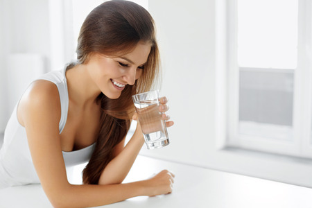 tomando agua: Salud, belleza, dieta concepto. Retrato de mujer feliz sonriendo joven que bebe refrescante agua en la mañana. Cuidado de la salud. Bebidas. Alimentación saludable. Estilo de vida saludable.