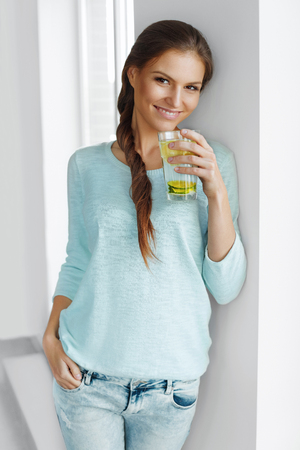 comiendo frutas: Estilo de vida saludable. Mujer Feliz Beber limonada fresca con limón, lima y menta en el vidrio. Detox agua. Saludable Agua vitamina fortificados. Alimentación saludable. Vitamina C. Concepto de dieta. Comida saludable.