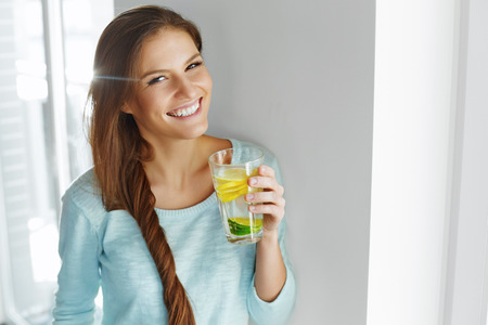 agua potable: Estilo de vida saludable, comida. Mujer Feliz Beber Verano Refrescante sabor a frutas infusión Agua Con orgánico fresco de limón, lima, menta. Detox agua vitamina fortificados. Alimentación saludable. Vitamina, Dieta concepto.