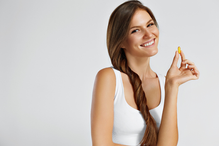 cod oil: Vitamins. Healthy Eating. Close Up Of Happy Beautiful Girl With Pill With Cod Liver Oil Omega-3. Nutrition. Healthy Lifestyle. Nutritional Supplements. Sport, Diet Concept. Vitamin D, E, A Fish Oil Capsules. Stock Photo