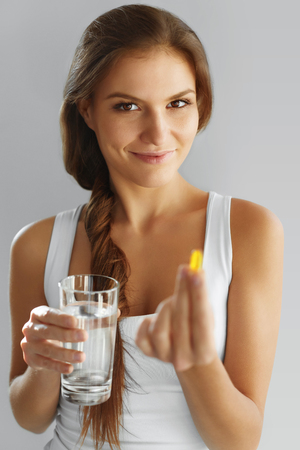 cod oil: Nutrition. Healthy Lifestyle. Close Up Of Happy Woman Holding Pill With Cod Liver Oil Omega-3. Medicine, Nutritional Supplements. Sport, Beauty And Diet Concept. Vitamin D, E, A Fish Oil Capsules.