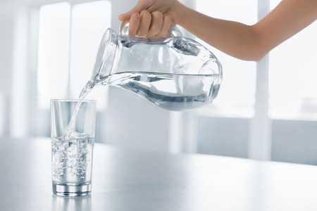 alimentos y bebidas: Beber agua. Echar mano de la mujer agua fresca y pura de la jarra en un vaso. Salud y dieta concepto. Estilo de vida saludable. Asistencia sanitaria y belleza. Hidratación. Foto de archivo