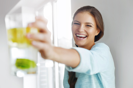 alimentos y bebidas: Healthy Lifestyle Concept, Diet And Fitness. Smiling Woman Drinking Refreshing Water With Fresh Organic Lemon , Lime, Mint. Detox Vitamin-fortified Water. Healthy Eating, Food. Vitamin, Diet Concept.