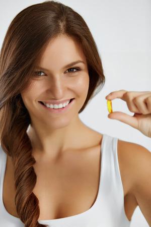 nutrici�n: Nutrici�n. Estilo de vida saludable. Cerca De La Mujer Feliz sostiene la p�ldora con h�gado de bacalao aceite Omega-3. Medicina, suplementos nutricionales. Deporte, Belleza y dieta concepto. La vitamina D, E, A petr�leo de pescados encapsula.