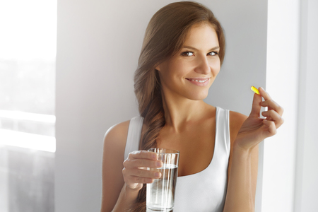 pill: Diet. Nutrition. Vitamins. Healthy Eating, Lifestyle. Close Up Of Happy Smiling Woman Taking Pill With Cod Liver Oil Omega-3 And Holding A Glass Of Fresh Water In Morning. Vitamin D, E, A Fish Oil Capsules.