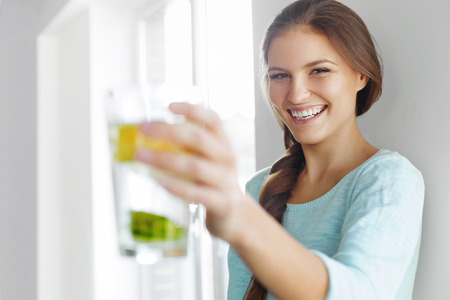 健康的なライフ スタイルのコンセプト、ダイエットやフィットネスです。新鮮なオーガニック レモン、ライム、ミントのさわやかな水を飲んでいる