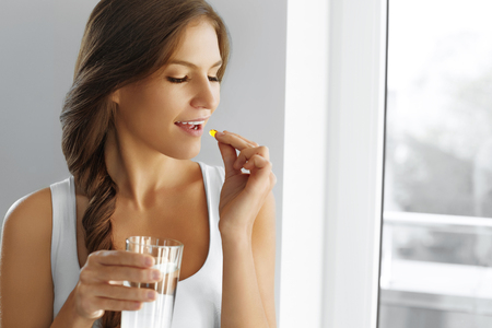 vitamins: Diet. Nutrition. Vitamins. Healthy Eating, Lifestyle. Close Up Of Happy Smiling Woman Taking Pill With Cod Liver Oil Omega-3 And Holding A Glass Of Fresh Water In Morning. Vitamin D, E, A Fish Oil Capsules.