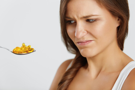woman eat: Diet Concept. Nutrition. Vitamins. Healthy Eating, Lifestyle. Close Up Of Woman With Spoon Full Of Fish Oil Omega-3 Capsules. Healthcare And Beauty. Vitamin D, E, A Cod Liver Oil Pills. Supplements.