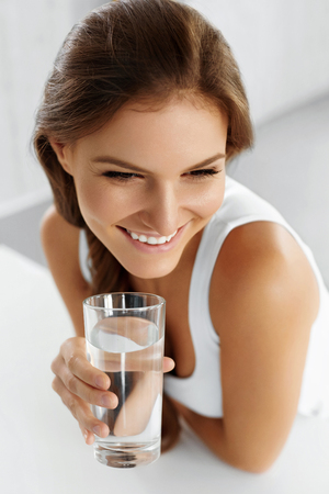 healthcare portrait: Health, Beauty, Diet Concept. Close-up Portrait Of Happy Young Woman Drinking Refreshing Pure Water From Glass. Healthcare. Drinks. Water. Healthy Eating. Healthy Lifestyle. Stock Photo