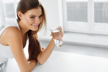 vida sana: Estilo de vida saludable. Retrato de mujer feliz sonriendo joven con el vidrio de agua dulce. Cuidado de la salud. Bebidas. Salud, belleza, dieta concepto. Alimentaci�n saludable. Hidrataci�n. Foto de archivo