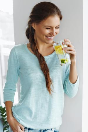 vaso con agua: Estilo de vida saludable. Mujer Feliz Beber limonada fresca con limón, lima y menta en el vidrio. Detox agua. Saludable Agua vitamina fortificados. Alimentación saludable. Vitamina C. Concepto de dieta. Comida saludable.