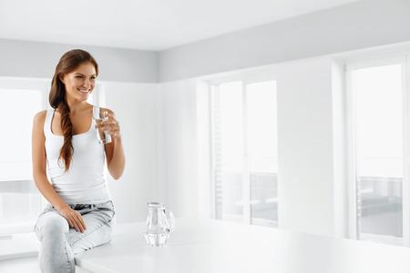 健康的なライフ スタイル。幸せな笑顔の若い女性の肖像画をさわやかな冷たい水のガラスをクローズ アップ。健康的な食事。ダイエット。ダイエッ