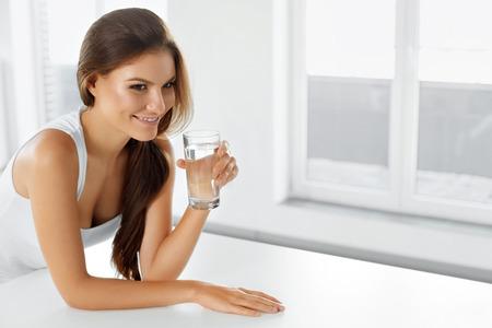 vasos de agua: Estilo de vida saludable. Retrato de mujer joven sonriente feliz con vaso de agua fresca. Cuidado de la salud. Bebidas. Salud, belleza, concepto de dieta. Alimentaci�n saludable. Foto de archivo