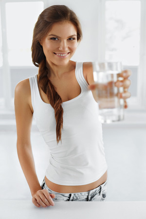 thirst: Water. Happy smiling woman drinking refreshing water. Healthcare. Drinks. Healthy eating. Healthy Lifestyle. Health, beauty, diet concept.  Hydratation. Stock Photo