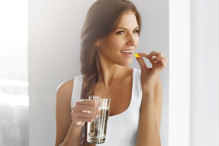 pastillas: Dieta. Nutrición. Vitaminas. Comida sana, Estilo de Vida. Primer plano de mujer feliz sonriendo Tomar la píldora con bacalao aceite de hígado de Omega-3 y con un vaso de agua dulce en la mañana. La vitamina D, E, A petróleo de pescados encapsula.