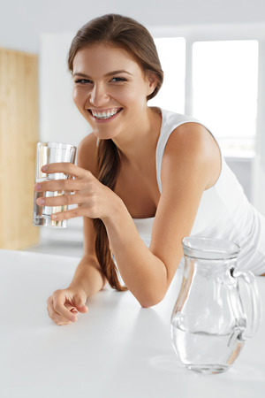 Beauty, Diet Concept. Happy Smiling Woman Drinking Fresh Crystal Clear Water From A Glass. Healthcare. Healthy Lifestyle And Eating. Health, Dieting, Fitness Concept. Drinks