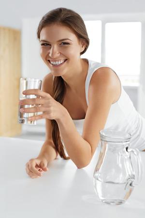 아름다움, 다이어트 개념입니다. 행복 한 미소 짓는 여자 유리에서 신선한 수정 같이 맑은 물 마시는. 건강 관리. 건강 한 라이프 스타일과 먹는입니다.