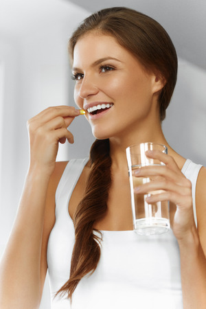 Vitaminas. Dieta saludable, alimentación, estilo de vida. Mujer sonriente feliz que toma la píldora con hígado de bacalao aceite Omega-3 y con un vaso de agua dulce. Asistencia sanitaria y belleza. La vitamina D, E, A petróleo de pescados encapsula. Nutrición. Foto de archivo - 47895070