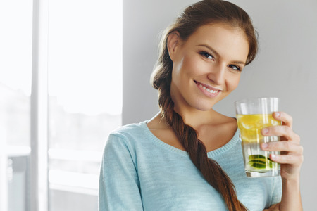 lemon water: Healthy Lifestyle, Food. Happy Woman Drinking Summer Refreshing Fruit Flavored Infused Water With Fresh Organic Lemon, Lime, Mint. Detox Vitamin-fortified Water. Healthy Eating. Vitamin, Diet Concept.