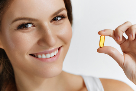 pill: Vitamins. Healthy Eating. Close Up Of Happy Beautiful Girl With Pill With Cod Liver Oil Omega-3. Nutrition. Healthy Lifestyle. Nutritional Supplements. Sport, Diet Concept. Vitamin D, E, A Fish Oil Capsules. Stock Photo