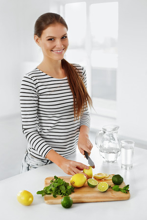 Healthy Food. Woman In The Kitchen Cutting Lemons And Limes. Healthy Lifestyle. Healthy Eating. Citrus Fruits. Vitamin C. Detox Water. Lemonade. Diet. Dieting Concept. photo