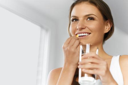 Des vitamines. Alimentation saine, de manger, de mode de vie. Happy Woman Smiling prise de la pilule Avec Cod Liver Oil Omega-3 et tenant un verre d'eau fraîche. Santé et beauté. La vitamine D, E, A Capsules d'huile de poisson. Nutrition. Banque d'images - 47895080