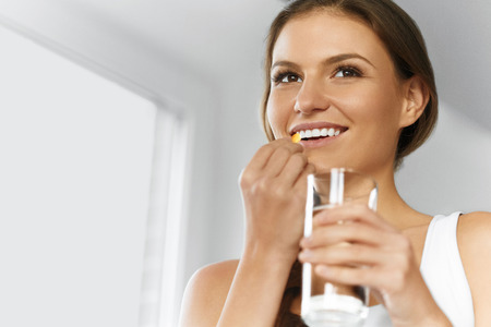 Vitamins. Healthy Diet, Eating, Lifestyle. Happy Smiling Woman Taking Pill With Cod Liver Oil Omega-3 And Holding A Glass Of Fresh Water. Healthcare And Beauty. Vitamin D, E, A Fish Oil Capsules. Nutrition. Foto de archivo