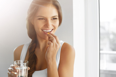 nutrition: Diet. Nutrition. Vitamins. Healthy Eating, Lifestyle. Close Up Of Happy Smiling Woman Taking Pill With Cod Liver Oil Omega-3 And Holding A Glass Of Fresh Water In Morning. Vitamin D, E, A Fish Oil Capsules.