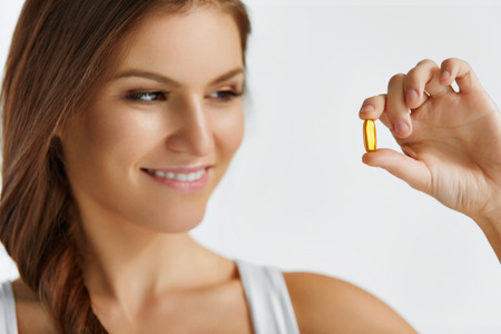 3 d: Vitamins. Healthy Eating. Close Up Of Happy Beautiful Girl With Pill With Cod Liver Oil Omega-3. Nutrition. Healthy Lifestyle. Nutritional Supplements. Sport, Diet Concept. Vitamin D, E, A Fish Oil Capsules. Stock Photo