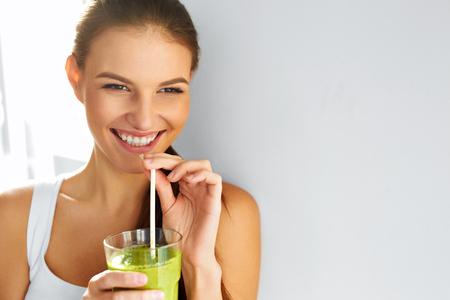 zumo verde: Comida sana. Feliz Hermosa Mujer Sonriente Beber Verde Vegetal Detox Smoothie. Dieta. Estilo de vida saludable, comida vegetariana. Toma jugo. Salud y belleza Concept.