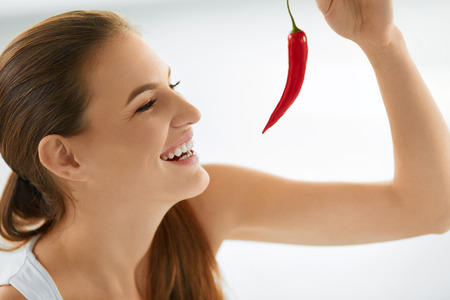 sexy food: Healthy Food. Close-up Of Beautiful Young Smiling Woman Holding Red Hot Chili Pepper. Healthy Lifestyle, Diet And Eating Concept.