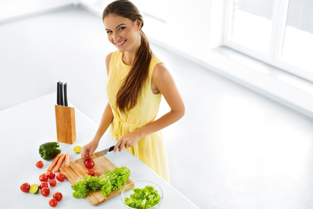 cutting vegetables: Healthy Eating. Close Up Beautiful Smiling Woman Cooking Fresh Organic Food And Making Vegetable Salad In Kitchen. Diet And Lifestyle Concept. Vegetarian Food Preparation. Nutrition.